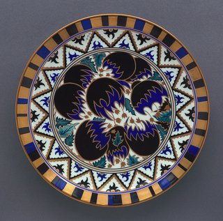 Circular form decorated in black, blue green and gold on white background. At center, conventionalized flowers, striped border.