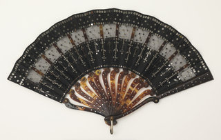 Éventail de poche (pocket fan). Leaf of black mousseline de soie. Obverse: applied with two bands of the same material and steel sequins of varying shapes. Tortoise shell sticks, each made of two separate pieces riveted together at shoulder forming a hinge and allowing the fan to be folded to half its length. Gorge shaped with S-curves and inlaid with round steel piqués. Metal bail.