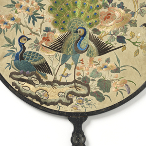 Hand screen with a round leaf and carved and pierced wood frame and handle. Silk leaf embroidered with silk in satin stitch showing peacocks and other birds among flowers. Two silk tassels.