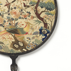 Hand screen with a round leaf and carved and pierced wood handle. Silk leaf embroidered with silk showing various bird species among trees and flowering bushes. Two silk tassels.