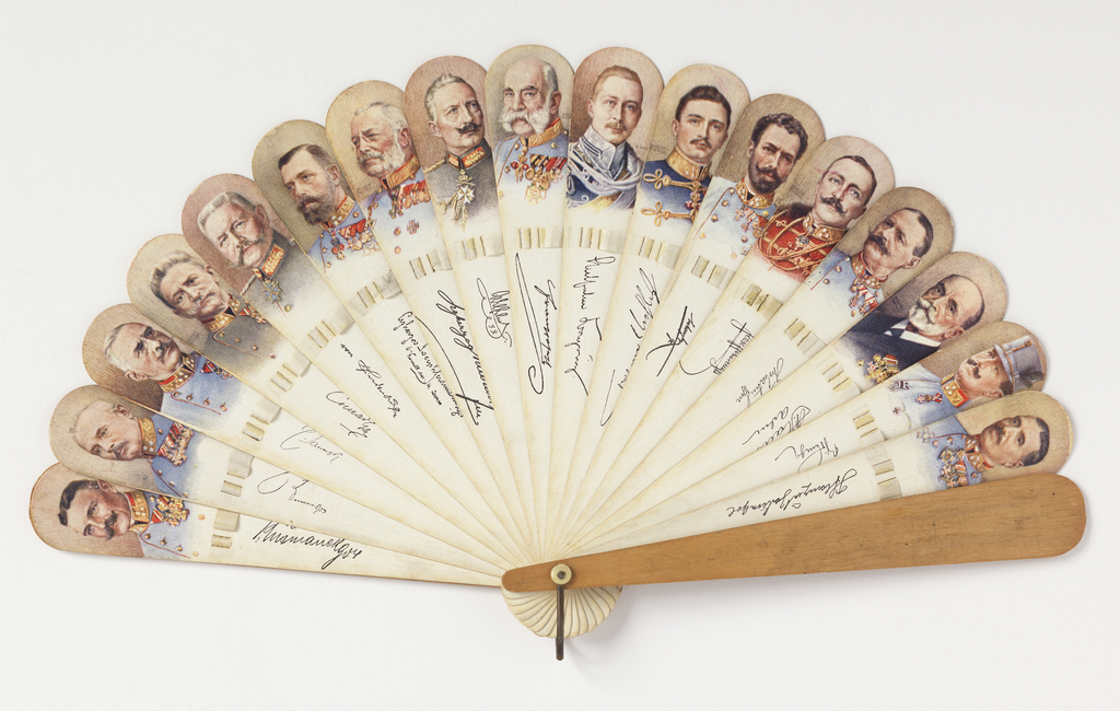 Brisé fan. Printed paper on wooden sticks showing portraits of military figures with signatures. Cream-colored connecting ribbon. Metal bail and ivory washer at rivet.