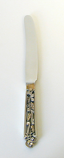Stainless steel blade with reeded gilt join to the openwork handle which encloses stylized silver scrolls and gilt-leaved stylized flowers. Terminal formed by three openwork e-scrolls and a gilt stylized flower.